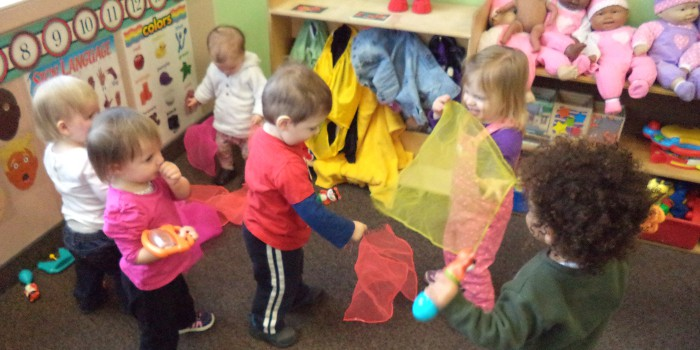 toddlers playing with scarves at kindergarten
